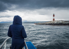 Back View Of Person In Hoodie Looking At Majestic Beacon While Standing On Ship In Stormy Sea On Overcast Day