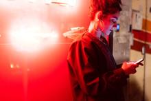 Attractive Stylish Lady Using Smartphone Near Neon Lights