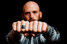 Bearded Serious Hipster In Shirt With Tattoos On Hand Showing Fists With Ring On Black Background