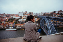 Back View Of Beautiful Female In Trendy Outfit Looking Away While Sitting Near Modern Bridge In Majestic Aged City