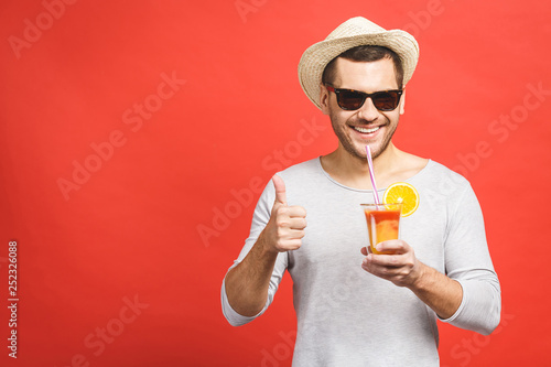 Portrait of attractive young man in hat and sunglasses standing and drinking orange juice over red background Fototapete