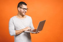 Confident Business Expert. Confident Young Handsome Man In Casual Holding Laptop And Smiling While Standing Against Orange Background.