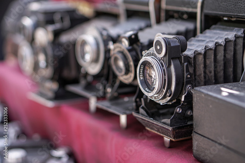 Vintage retro photo equipment at a flea market. Film photo camera on a red background. Stock photography, photo.