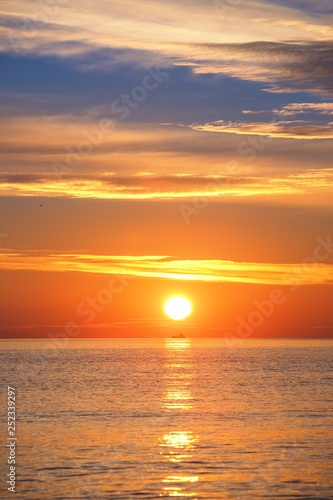 Photo sur Toile Orange eclat Sunrise over the sea with sailing cargo ship,. Transportation. Logistics. Shipping.