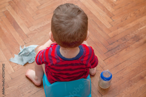 Photo little baby sitting on chamber pot with toilet paper and pacifier on a brown bac