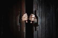 Hands Open The Wooden Door From The Inside Of The Dark Room.