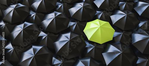 Foto  Unique green umbrella among many dark ones