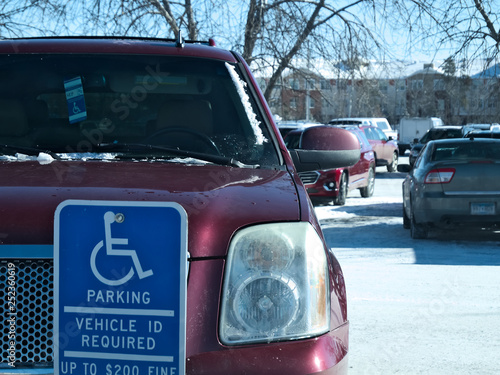 Valokuva  Handicapped parking sign posted in snow covered parking lot and red car with handicapped placard in window