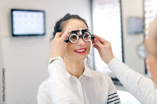 Ophthalmologist putting test glasses phoropter and checking
