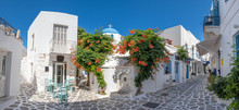 Panorama Of The Beautiful Narrow Street In Greece With Cozy Outdoor Cafe And Traditional Greek Church In Parikia Town On Paros Island, Cyclades