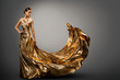 canvas print picture - Woman Gold Dress, Fashion Model in Long Waving Fluttering Gown, Young Girl Beauty Studio Portrait