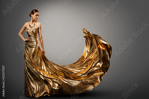 Vászonkép Woman Gold Dress, Fashion Model in Long Waving Fluttering Gown, Young Girl Beaut