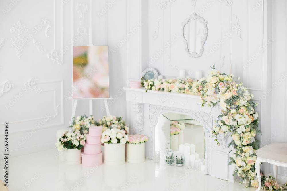 Fototapeta Elegant white fireplace full of flowers. Elegant white room decorated with easel and hat boxes. Wedding decorated area. Vintage decor in light interior