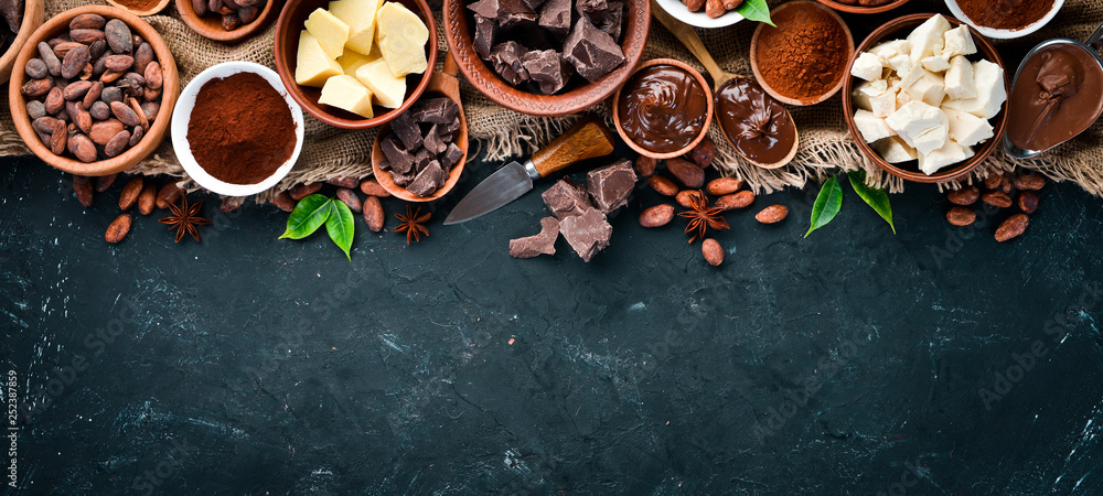 Fototapety, obrazy: Cocoa beans, chocolate, cocoa butter and cocoa powder on a black background. Top view. Free copy space.