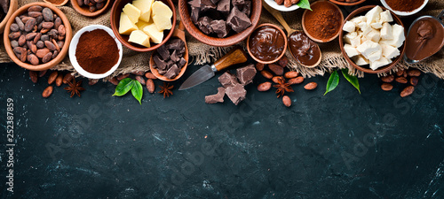 Cocoa beans, chocolate, cocoa butter and cocoa powder on a black background Fototapet