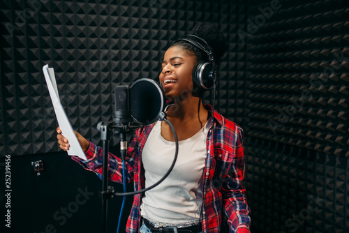 Young woman songs in audio recording studio - 252391456