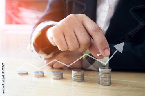 Fototapeta Woman putting coins on stack with holding money, Concept business, finance, money saving and investment obraz