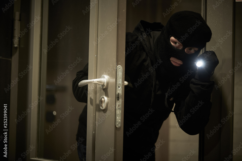 Fototapeta Burglar thief in mask. break-in of an apartment.