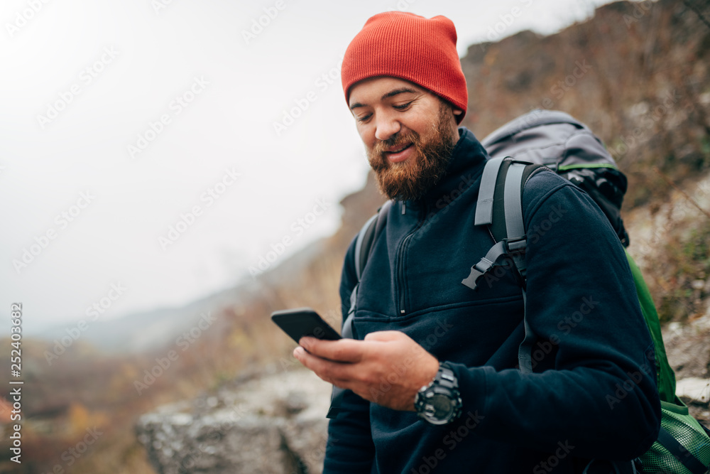 Fototapety, obrazy: Young bearded man smiling and sending messages for his family from his cellphone, during hiking in mountains. Traveler bearded man in red hat using mobile phone application. Travel and lifestyle