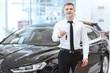 Cheerful young car dealer holding car keys at the dealership