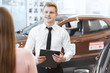 Young couple choosing a car with salesman at the dealership