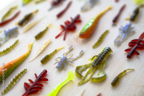 Fotografía  Colorful silicone fishing baits with plummets on wooden table