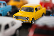 Stacked Toy Cars And A 70s Model Yellow Toy Car In The Focus.
