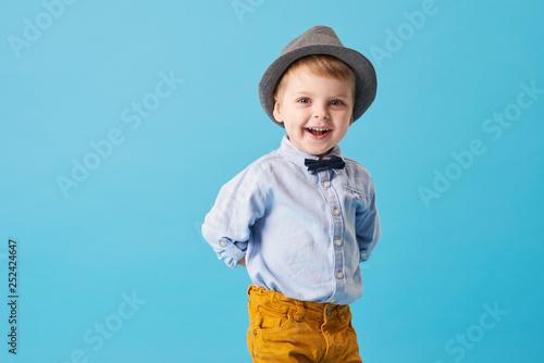 Portrait of happy joyful  little boy isolated on blue background Wallpaper Mural