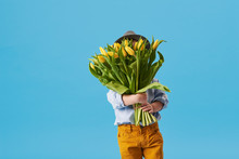 Cute Smiling Child Holding A Beautiful Bouquet Of Yellow Tulips In Front Of His Face Isolated On Blue. Little Toddler Boy Gives A Bouquet To Mom