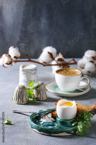 Fotografía  Breakfast with cup of coffee and soft boiled egg, served in green ceramic egg cup with salt, pepper and toasted bread, jug of cream and cotton flowers over grey blue table