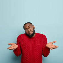 Why Not To Choose This? Clueless Bearded Unshaven Afro American Guy Shruggs Shoulders, Being Torubled To Understand, Tries To Understand What Somebody Meant, Raises Palms, Dressed In Red Clothes