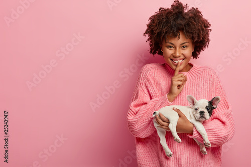 Obraz Shush, dont bother my little puppy. Positive dark skinned girl cares of french bulldog, carries it on hands, wears oversized jumper, models over pink background, feels optimistic. Animals concept - fototapety do salonu