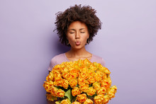 Beautiful Dark Skinnned Curly Woman Holds Nice Bouquet Of Yellow Tulips, Folds Lips, Closes Eyes, Wants To Kiss Beloved Boyfriend And Say Thank You For Flowers, Stands Against Purple Background.