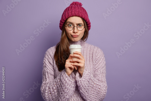 Fotografía  Unhappy woman wears glasses, hat and sweater, enjoys hot drink after lectures, listnes interlocutor with puzzlement, isolated over purple studio wall