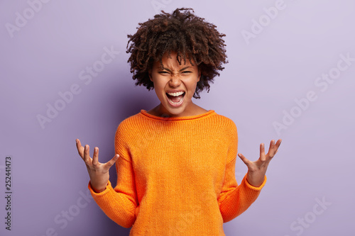 Fotografie, Obraz  Angry annoyed female gestures with annoyance, screams loudly, expresses irritation, wears casual orange jumper, reproaches partner in betrayal, isolated over purple studio wall