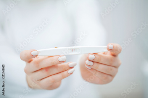 Woman Holding Pregnancy Test with positive results Wallpaper Mural