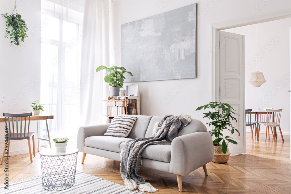 Fototapety, obrazy: Modern scandianvian living room with design sofa with elegant blanket, coffee table and bookstand on the white wall. Brown wooden parquet. Concept of minimalistic interior.
