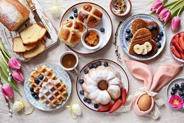 Uskršnji svečani desertni stol s vrućim križanjima, kolačima, vaflima i palačinkama. Pogled odozgo