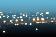 Defocused or blurred image of multi-colored lights in the city streets. Abstract background, selective focus.