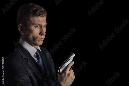 Fotografie, Obraz  Portrait of attractive serious agent with gun in dark business suit and bright b