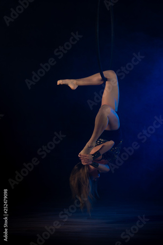 Foto op Plexiglas Gymnastiek gymnast girl aerial acrobatics on the ring on the background of blue smoke in the dark