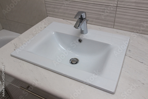 Fotografía  Ceramic white washbasin with stainless faucet mounted on a marble worktop against a background of gray large wall ceramic tiles