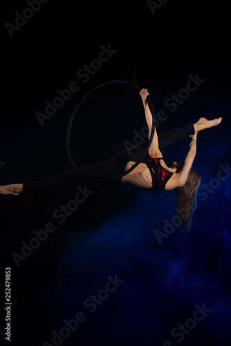 Spoed Fotobehang Muziek gymnast girl aerial acrobatics on the ring on the background of blue smoke in the dark
