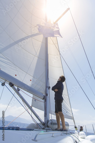 Photo A man on a sailing yacht stands with his back and looks at the open sails