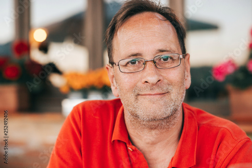 Outdoor portrait of 50 year old man wearing red polo shirt and eyeglasses