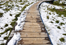 Perspective Of A Wooden Path/ Trail/ Walk In Trentino (Alps, Italy) On A Suny Morning During My Trip To Val Di Fassa. The Snow Is Melting Because Of The Spring Thaw; Underneath There Is The New Grass.