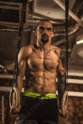 Fényképezés  Male athlete working out on gymnastics rings at the crossfit gym