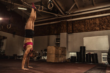 Athletic Young Woman Doing A Handstand At The Gym