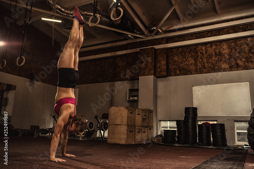 Athletic young woman doing a handstand at the gym Canvas Print