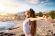 canvas print picture - Junge, blonde Frau streckt ihre Arme am Strand aus und genießt die Freiheit und Ruhe